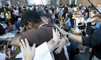 Brittney Cain-Conley, lead organizer for Congregate Charlottesville, with hat, gets a hug from a supporter after she addressed the crowd during a vigil on Sunday, Aug. 13, 2017