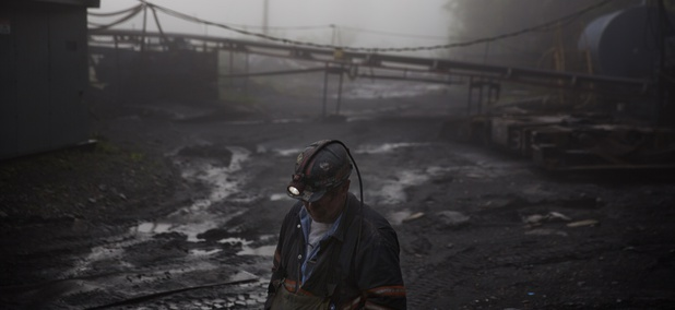 A coal miner walks through the morning fog in Welch, W.Va. in May of 2016.
