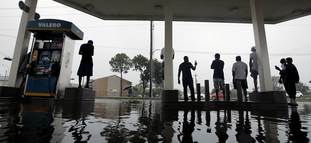People watch heavy rain caused by Harvey from the relative safety of a flooded gas station on Sunday, Aug. 27, 2017, in Houston.
