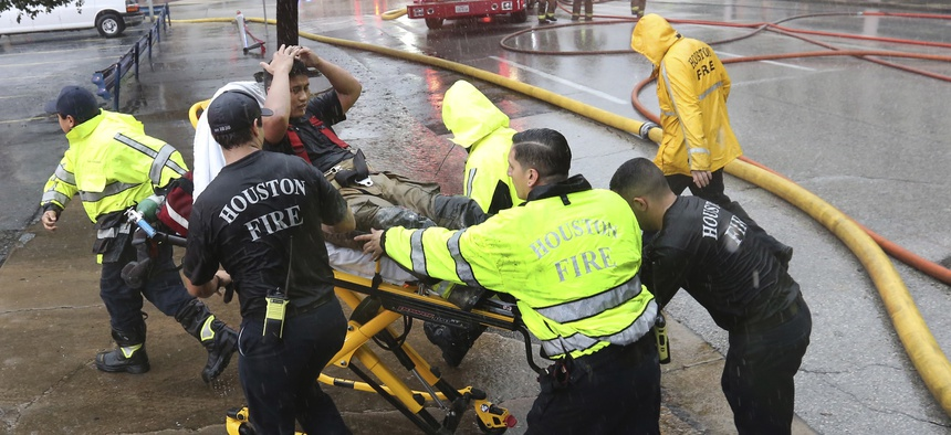 Rain from Tropical Storm Harvey falls as a firefighter is wheeled to a waiting ambulance after he became fatigued while fighting an office building fire in downtown in Houston, Texas, Monday, Aug. 28, 2017.