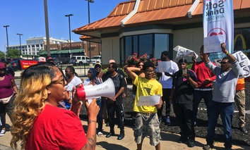"Gennice Mackey uses a bullhorn Thursday to lead a chant of ""Save the Raise!"" outside a McDonald's restaurant in St. Louis."