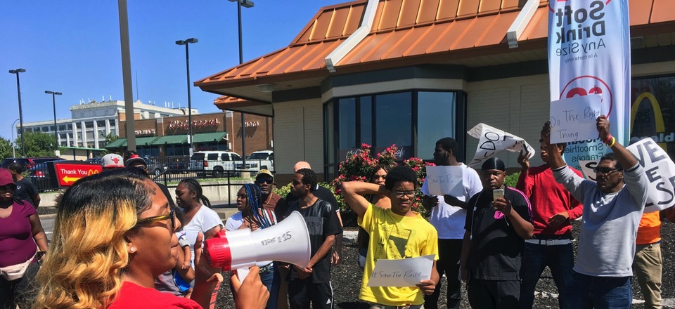 """Gennice Mackey uses a bullhorn Thursday to lead a chant of """"Save the Raise!"""" outside a McDonald's restaurant in St. Louis."""