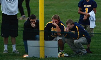 Football players and other student athletes pause at a makeshift memorial on the football field at Shoreham Wading Hill High School in New York in October 2014.