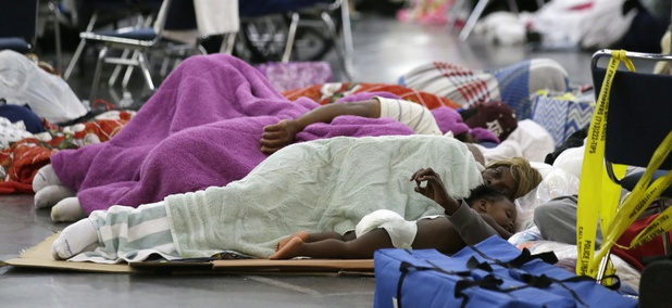 People sleep on the floor at the George R. Brown Convention Center that has been set up as a shelter for evacuees escaping the floodwaters from Tropical Storm Harvey in Houston, Texas, Tuesday, Aug. 29, 2017.