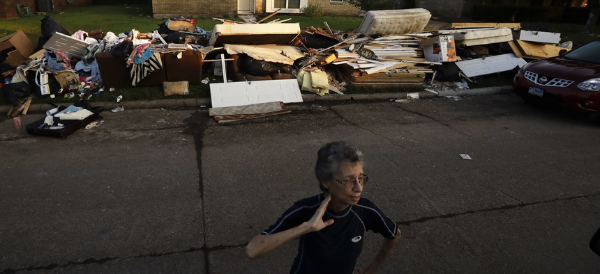 Joan Finmore looks out as she takes a break from sorting items at a friend's flooded home Saturday, Sept. 2, 2017, in Houston.
