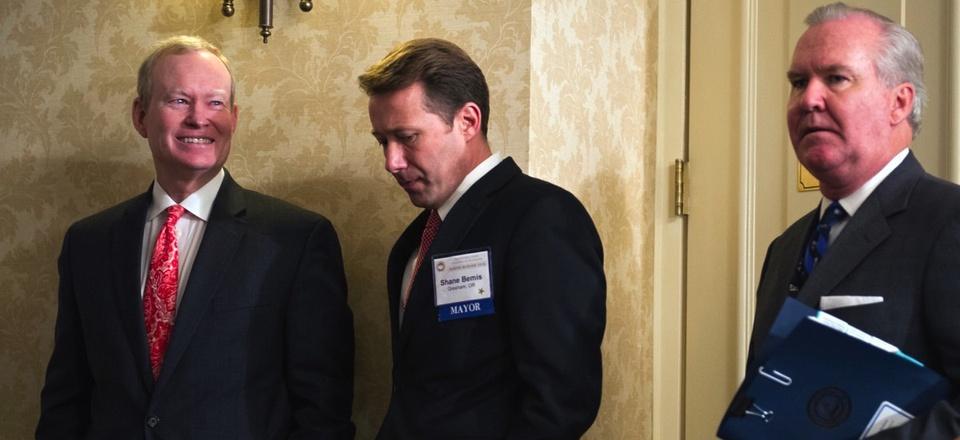 The U.S. Conference of Mayors' former president, Oklahoma City Mayor Mick Cornett, left, and Gresham, Oregon Mayor Shane Bemis, center, wait for a news conference to begin in Washington, D.C. in Jan. 2016.