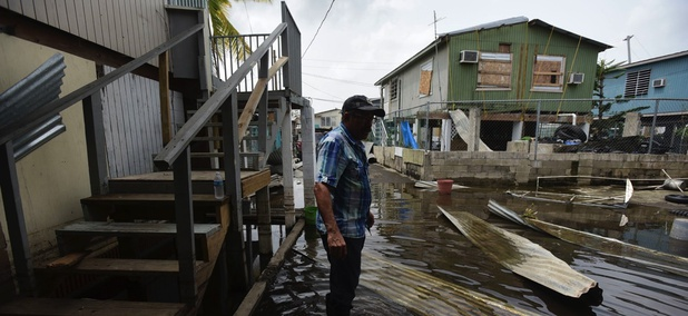 Juana Matos resident Hector Rosa walks through a flooded area Wednesday after the passing of Hurricane Maria through Puerto Rico.