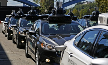 In September 2016, a group of self-driving Uber vehicles position themselves to take journalists on rides during a media preview at Uber's Advanced Technologies Center in Pittsburgh.