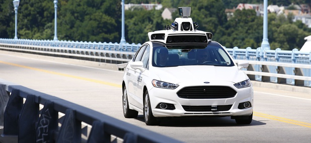 Uber employees test a self-driving Ford Fusion hybrid car, in Pittsburgh, during August 2016.