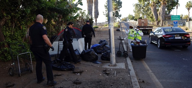 Police officers remove a tent left by the homeless during efforts to sanitize neighborhoods to control the spread of hepatitis A, in San Diego.