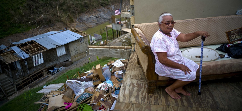 Juana Sortre Vazquez sits on her soaked couch in what remains of her home, destroyed by Hurricane Maria, in the San Lorenza neighborhood of Morovis, Puerto Rico.