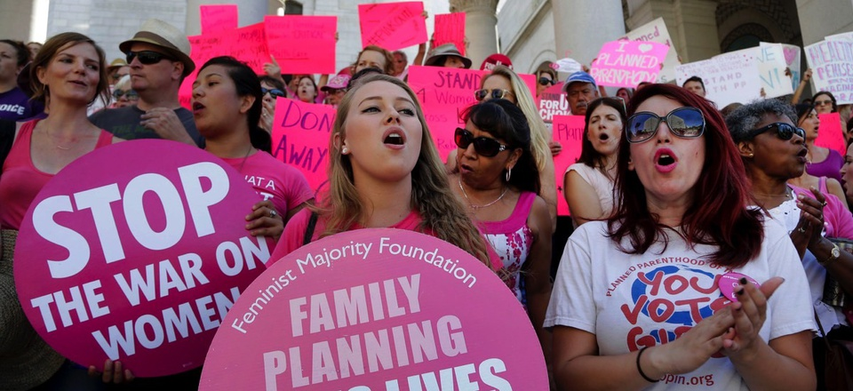 """Planned Parenthood supporters rally for women's access to reproductive health care on """"National Pink Out Day'' at Los Angeles City Hall in Sept. 2015."""