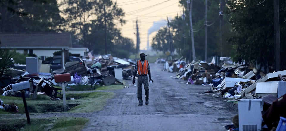A man walks past debris from homes on his street damaged in flooding from Hurricane Harvey, in Port Arthur, Texas, during September 2017.