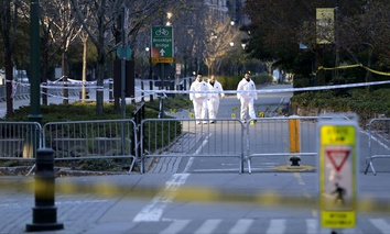 Emergency officials walk near evidence markers on the west side bike path in lower Manhattan, New York, Wednesday, Nov. 1, 2017.