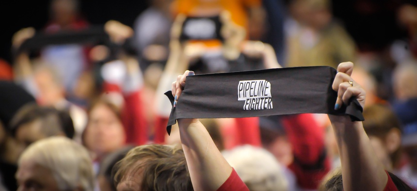 Opponents to the Keystone XL pipeline hold arm bands at a hearing Saturday, April 18, 2013 in Grand Island, Nebraska.