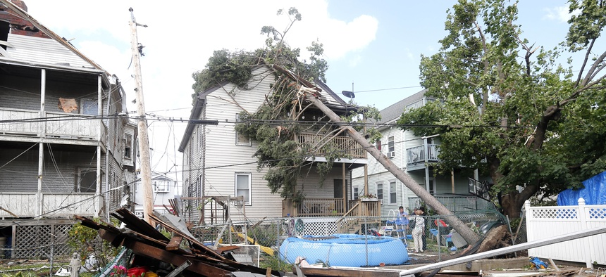 People observe the damage in the back of several houses in Revere, Mass. Monday, July 28, 2014, after a tornado touched down.