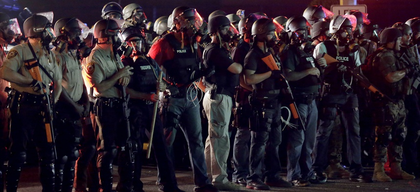 Police in riot gear mobilize during a standoff with protesters Monday.