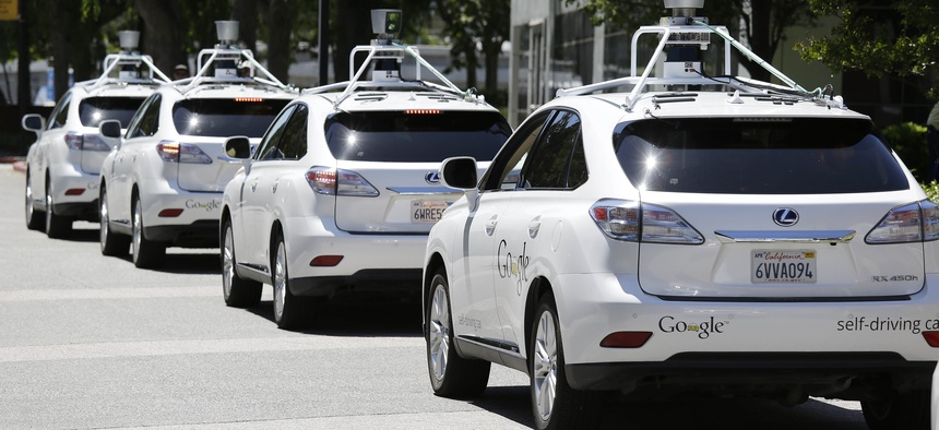 In this photo taken Wednesday, May 14, 2014, a row of Google self-driving cars are shown outside the Computer History Museum in Mountain View, Calif.