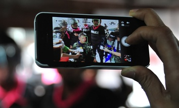 A journalist uses a smartphone to capture an interview of activist Capt Songklod Chuenchupol after his arrest during an anti-amnesty bill rally on Aug 7, 2013 in Bangkok, Thailand.