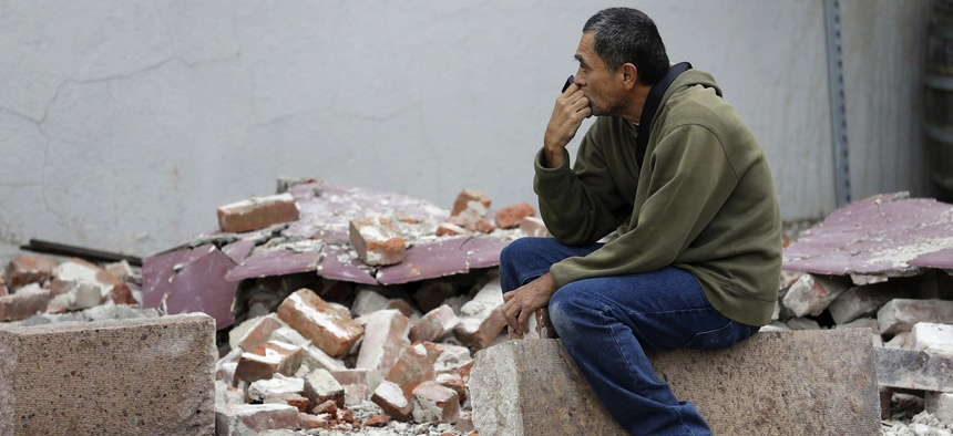 Ron Peralez, of Vacaville, Calif., sits on rubble and looks at earthquake-damaged buildings Monday, Aug. 25, 2014, in Napa, Calif.