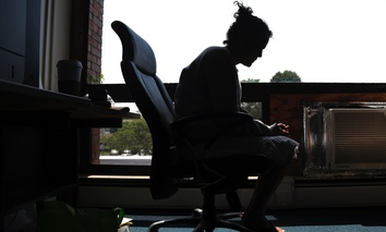 In this July 10, 2015, photo, a woman speaks to The Associated Press inside the police station in Gloucester, Mass. The woman voluntarily came to the police for help kicking her heroin addiction.
