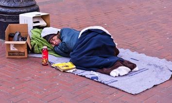 A homeless man sleeps on Market Street in San Francisco.