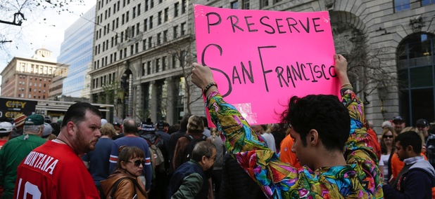 Shane Zaldivar holds up a sign as crowds jam Market Street trying to enter Super Bowl City Saturday, Feb. 6, 2016, in San Francisco.