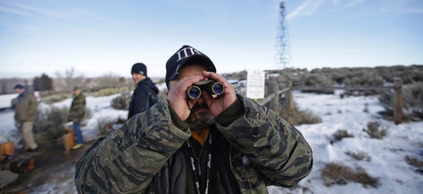 Sean Anderson, a supporter of the group that occupied the Malheur National Wildlife Refuge, looks through binoculars at the front gate on Jan. 6 near Burns, Ore.
