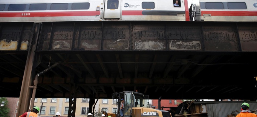 While a Metro-North train passes above, work continues underneath the tracks at the site of a fire in New York on Wednesday.