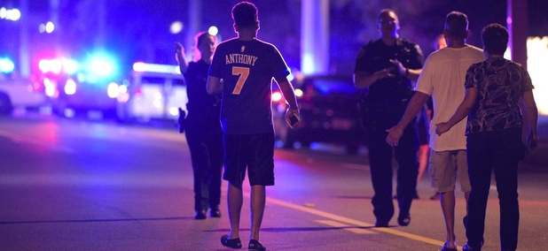 Orlando Police officers direct family members away from a shooting involving multiple fatalities at the Pulse Orlando nightclub on Sunday.