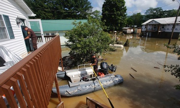 West Virginia Natural Resources police officer Chris Lester, left, walks into the top floor of a flooded home as he and Lt. Dennis Feazell search homes in Rainelle on Saturday.