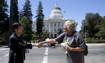 State Sen. Richard Pan (D-Sacramento) shakes hands with  Debbie Bartley near the California State Capitol in Sacramento.
