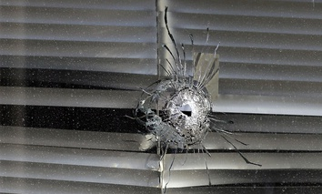 A bullet hole is seen in a window at El Centro College, Thursday, July 14, 2016, in Dallas. Five police officers were killed and seven others wounded when Micah Johnson opened fire during a planned protest last Thursday.