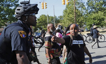 A marcher talks to a Cleveland Police officer during a march against racism and injustice before the Republican National Convention, Saturday, July 16, 2016 in Cleveland, Ohio.