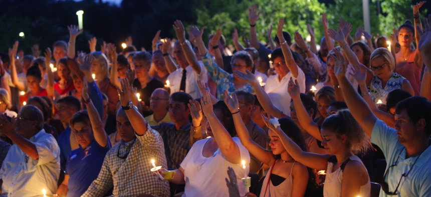 People attend a candlelight vigil for Baton Rouge police officer Matthew Gerald, at the Healing Place Church in Baton Rouge on Monday.