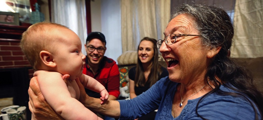 Jill Breen, a midwife, examines 10-week-old Maggie Dickson while her parents Jamie and Shannon Dickson look on, at their home in Waterville, Maine.