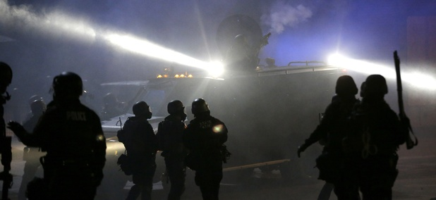 Police in riot gear stand around an armored vehicle in Ferguson, MO after the fatal shooting of Michael Brown by white police officer Darren Wilson.