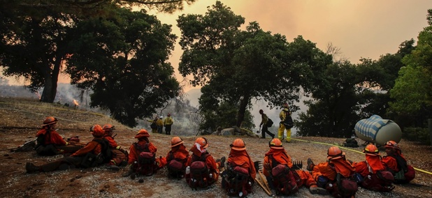 Members of hand crew rest on a hillside near Placenta Canyon Road as a wildfire burns in Santa Clarita, California, on Sunday.