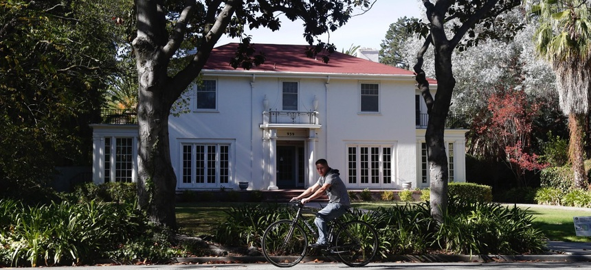 A man cycles past a large home in Palo Alto, California.