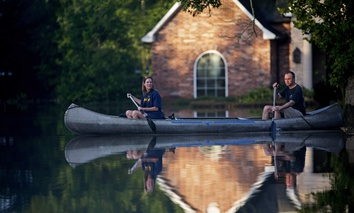 Danny and Alys Messenger canoe away from their flooded home after reviewing the damage in Prairieville, La., Tuesday, Aug. 16, 2016.