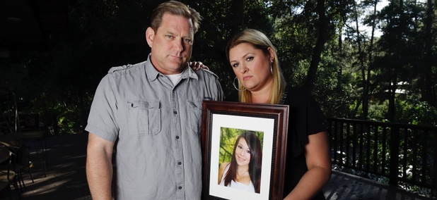 Larry Pott, left, and his wife Lisa pose for a portrait holding a picture of their daughter Audrie in Saratoga, Calif. Audrie Pott committed suicide in September 2012 after being sexually assaulted by three boys during a house party in Saratoga.