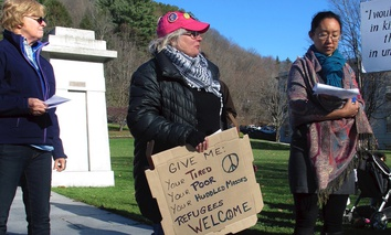 Crystal Zevon, center, holds a sign on Nov. 20, 2015, at a rally outside the Statehouse in Montpelier, Vt., where she supported bringing resettling Syrian refugees.