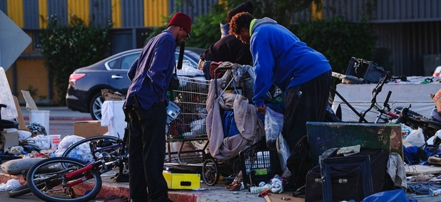 Homeless men sort through their belongings on a traffic island near downtown Los Angeles.