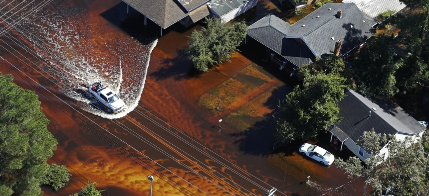 A truck drives through floodwaters from Hurricane Matthew in Lumberton, N.C., Wednesday, Oct. 12, 2016.