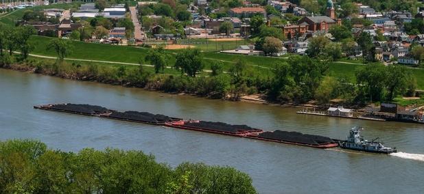 A coal barge floats past Dayton, Kentucky.