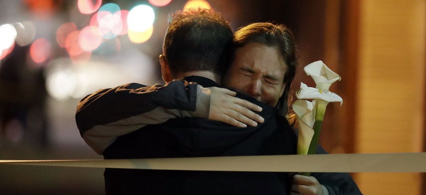 Mourners embrace near the site of Friday night's warehouse fire in Oakland, Calif.