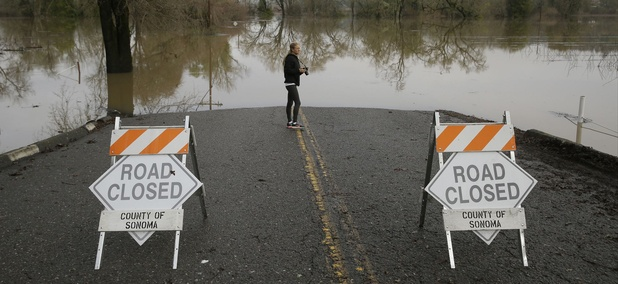 Michelle Wolfe, who had to evacuate her nearby mobile home, looks out toward flooded vineyards in the Russian River Valley, Monday, Jan. 9, 2017, in Forestville, Calif.