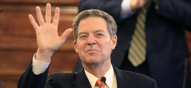 Gov. Sam Brownback waves to guests before delivering his state of the state address to a joint session of the Kansas legislature in Topeka, Kan., Tuesday, Jan. 10, 2017.