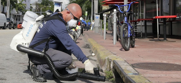 "Miami-Dade mosquito control inspector Yasser ""Jazz"" Compagines sprays a chemical mist into a storm drain, Tuesday, Aug. 23, 2016, in Miami Beach, Fla."