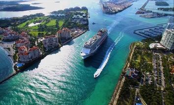 A cruise ship exits Miami into the Atlantic Ocean via the Government Cut canal.